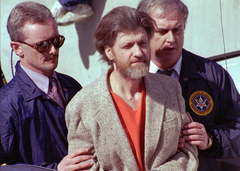 FILE — In this April 4, 1996 file photo Theodore John Kaczynski is flanked by federal agents as he is led to a car from the federal courthouse in Helena, Mont. A federal grand jury in San Francisco indicted Vladislav Victorvic Timoshchuk, on charges of mailing two envelopes containing ricin to Pelican Bay State Prison, officials announced on Friday Feb. 21, 2020. Last year the federal Bureau of Prisons intercepted a Christmas card from Timoshchuk, now living in Belarus, to Kaczynski, the convicted Unabomber, which authorizes say Timoshchuk discussed his plan to mail ricin to the United States. Kaczynski is serving a life sentence in a federal prison in Colorado for carrying out a series of mail bombings that killed three people. (AP Photo/John Youngbear, File)