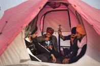 From left to right, Sahajpal Singh, Arjun Singh, Jagmohan Singh and Gurdayal Singh chat as they sit inside a tent pitched on a highway during a protest against new farm laws, at the Delhi-Haryana state border, India, Tuesday, Dec. 1, 2020. Instead of cars, the normally busy highway that connects most northern Indian towns to the capital is filled with tens of thousands of protesting farmers, many wearing colorful turbans. Their convoy of trucks, trailers and tractors stretches for at least three kilometers (1.8 miles). Inside, they have hunkered down, supplied with enough food and fuel to last weeks. (AP Photo/Altaf Qadri)