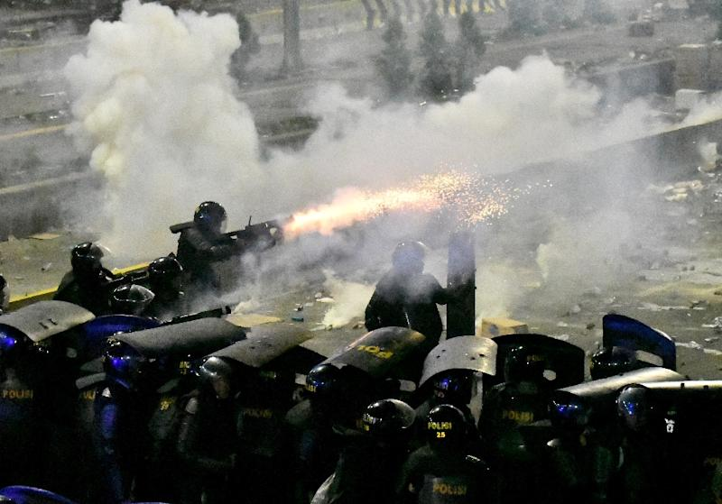Indonesian riot police in Jakarta fire tear gas at protesters demonstrating against the re-election of Indonesian President Joko Widodo (AFP Photo/GOH Chai Hin)