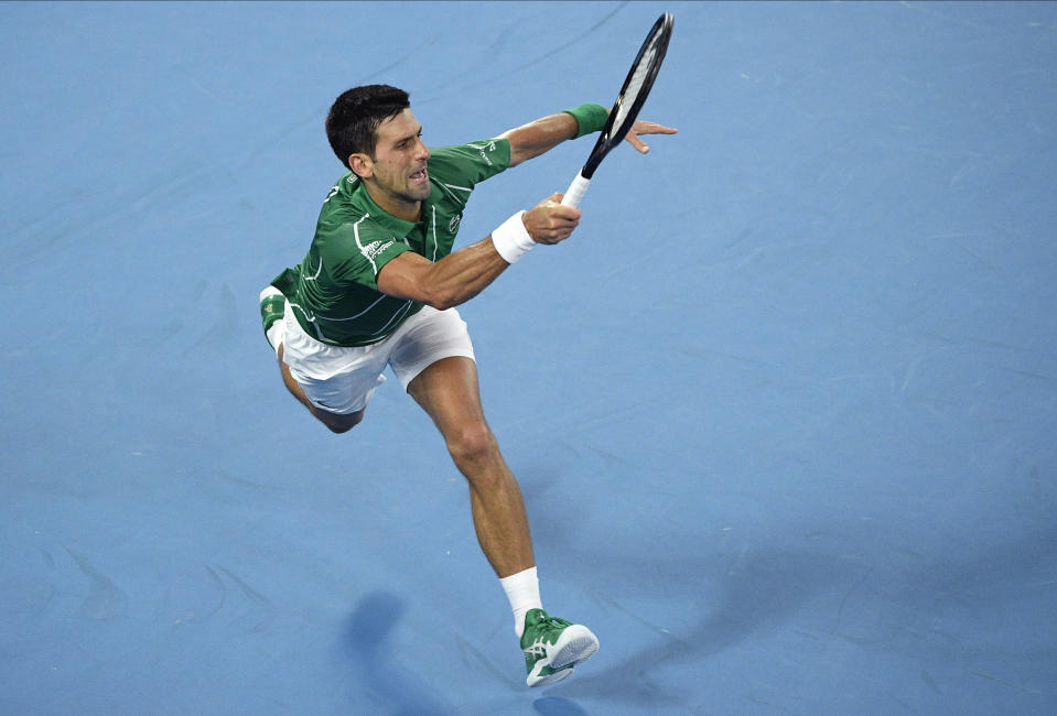 Serbia's Novak Djokovic makes a forehand return to Germany's Jan-Lennard Struff during their first round singles match at the Australian Open tennis championship in Melbourne, Australia, Monday, Jan. 20, 2020. (AP Photo/Andy Brownbill)