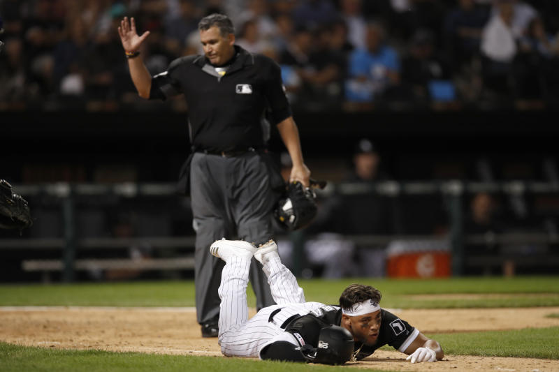 Home plate umpire Manny Gonzalez, left, calls out Chicago White Sox's Yoan Moncada, who tripped and fell out of the batter's box on a groundout during the seventh inning of a baseball game against the Texas Rangers on Thursday, Aug. 22, 2019, in Chicago. (AP Photo/Jeff Haynes)