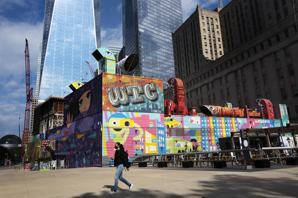 A woman walks by the colorful murals that surround the foundation for 2 World Trade Center, Wednesday, Sept. 8, 2021 in New York. Planned as the second tallest skyscraper at the site, 2 World Trade Center, might someday reach 80 stories. Developer Larry Silverstein has said he wants to sign an anchor tenant for the tower before starting construction. (AP Photo/Mark Lennihan)