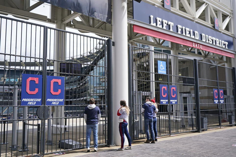 Cleveland Indians fans look into the ballpark after a baseball game between the Toronto Blue Jays and the Cleveland Indians was postponed due to inclement t weather, Saturday, May 29, 2021, in Cleveland. The game will be rescheduled as a traditional doubleheader Sunday. (AP Photo/Tony Dejak)