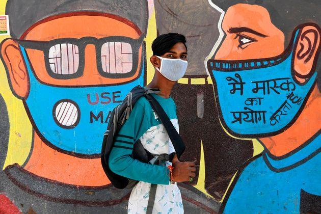 A man walks past a mural representing frontline warriors of the Covid-19 coronavirus, painted on the wall of a dumping ground in New Delhi on September 29, 2020.