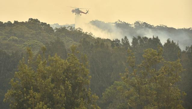 A helicopter drops water on a bushfire just outside Batemans Bay in New South Wales on Jan. 2, 2020. (Photo by PETER PARKS / AFP) (Photo by PETER PARKS/AFP via Getty Images)