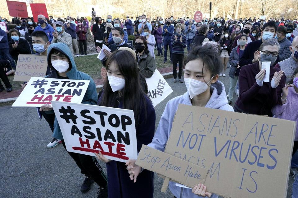 Protesters stand holding signs in support of Stop Asian Hate