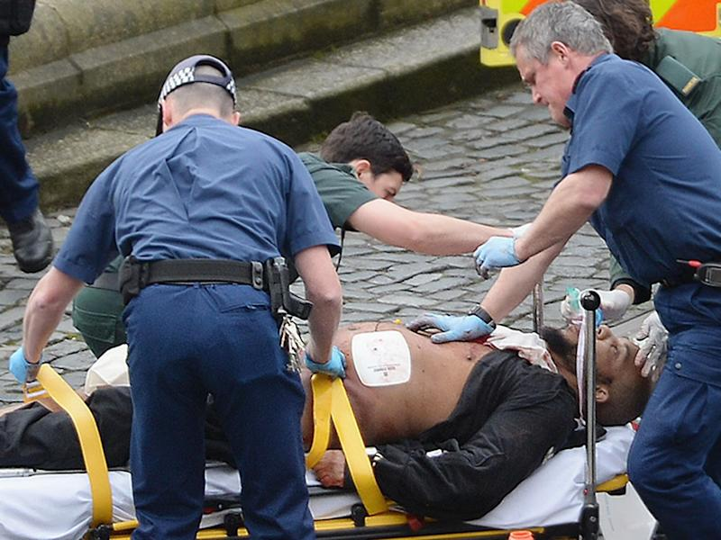 Emergency services attend to London attacker Khalid Masood outside Parliament yesterday: PA