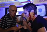 <p>A Juventus' fan walks injured as the fans gathered in San Carlo Square run away following panic created by the explosion of firecrackers as they was watching the match on a giant screen on June 3, 2017. (Giorgio Perottino/Reuters) </p>