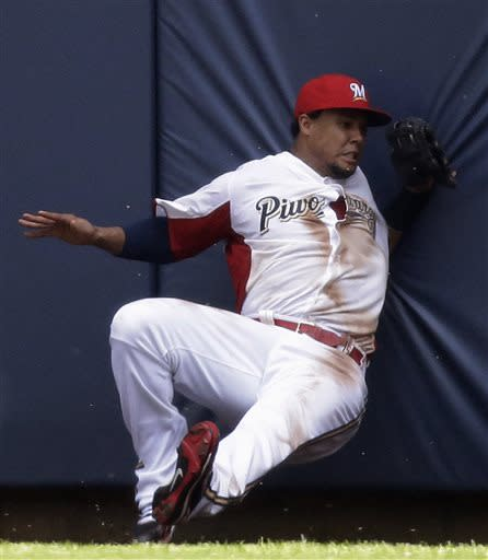 Milwaukee Brewers center fielder Carlos Gomez hits the wall after catching a ball hit by Atlanta Braves' Andrelton Simmons during the fourth inning of a baseball game on Sunday, June 23, 2013, in Milwaukee. Gomez left the game. (AP Photo/Morry Gash)
