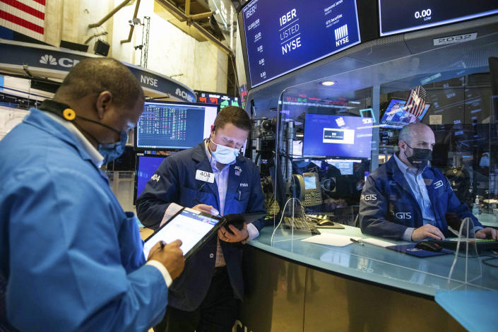 In this photo provided by the New York Stock Exchange, traders work on the floor, Friday, Feb 26, 2021. Stocks wobbled between small gains and losses on Wall Street Friday as rising technology stocks offset a slide in banks and energy companies. (Courtney Crow/New York Stock Exchange via AP)