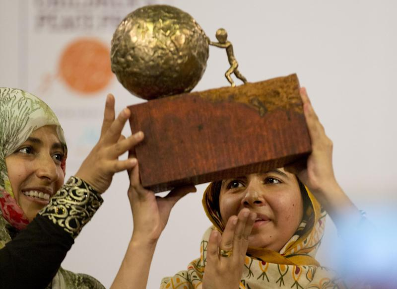 Pakistani teenager Malala Yousafzai, right, who was shot and injured by the Taliban for advocating girls' education, is awarded the International Children's Peace Prize 2013 by 2011 Nobel Peace Prize winner Tawakkol Karman of Yemen, left, during a ceremony in the Hall of Knights in The Hague, Netherlands, Friday Sept. 6, 2013.(AP Photo/Peter Dejong)
