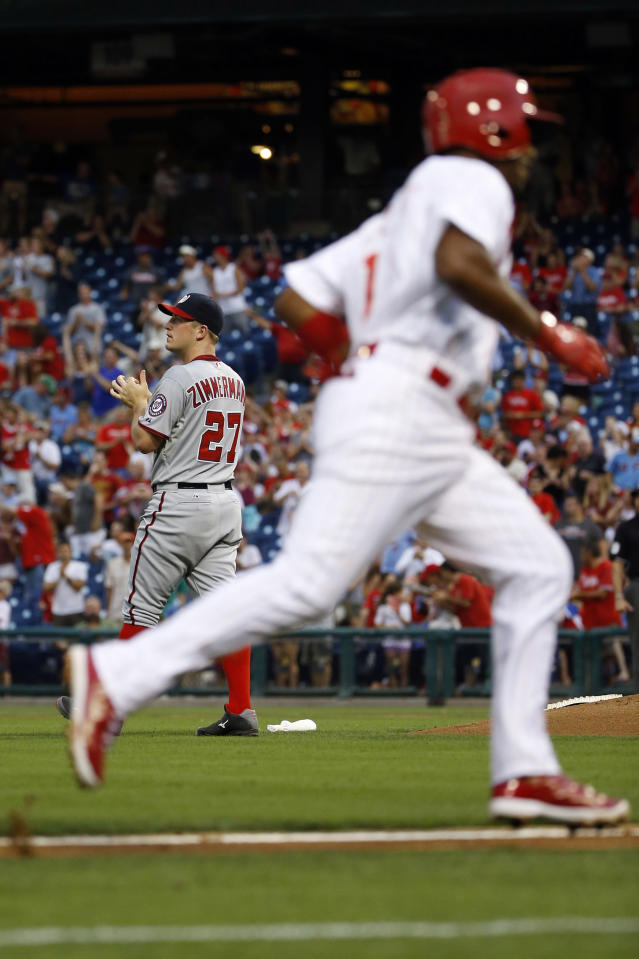 Washington Nationals starting pitcher Jordan Zimmermann, left, watches the scoreboard after giving up a two-run home run to Philadelphia Phillies' Jimmy Rollins during the third inning of a baseball game, Friday, July 11, 2014, in Philadelphia. (AP Photo/Matt Slocum)