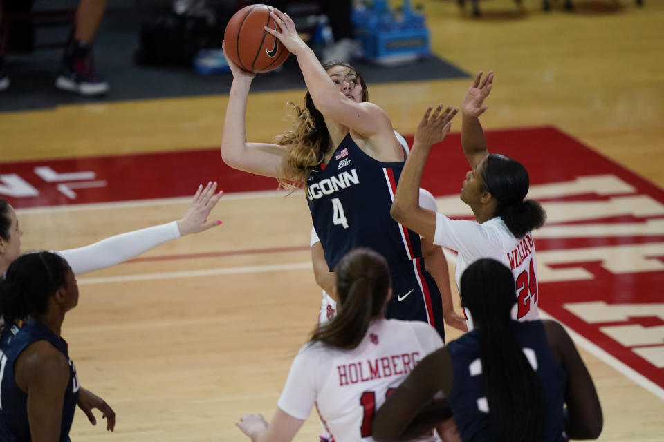 FILE - Connecticut guard Saylor Poffenbarger (4) is defended by St. John's guard Danaijah Williams (24) and forward Cecilia Holmberg (11) during the fourth quarter of an NCAA college basketball game in New York, in this Wednesday, Feb. 17, 2021, file photo. Players like Connecticut's Saylor Poffenbarger are not only gaining a head start and valuable experience in their college basketball careers as early enrollees out of high school, they have been counted upon to help women's teams across the country keep their seasons going when players are held out for COVID-19 protocols. Now, some will make their March Madness debuts on the stage in the NCAA Tournament.(AP Photo/Kathy Willens, File)