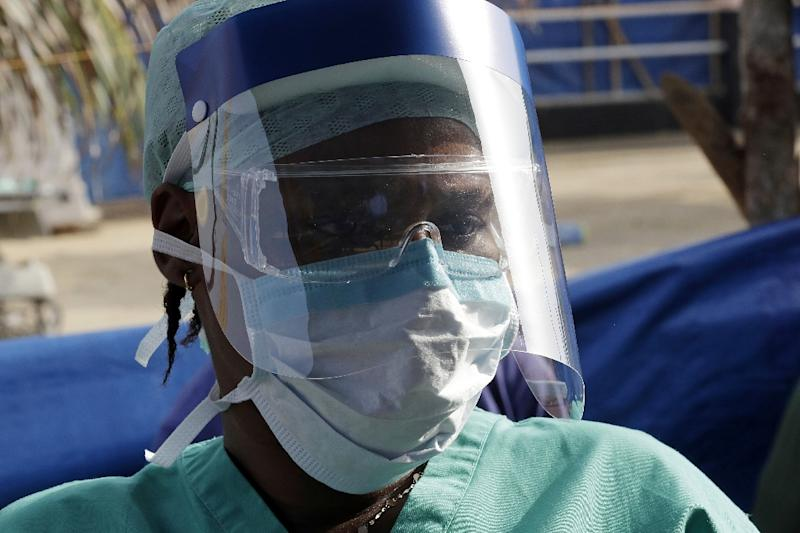 A medic listens on as UN Secretary General Ban Ki-moon gives a speech during his visit an Ebola treatment unit in Sierra Leone on December 19, 2014