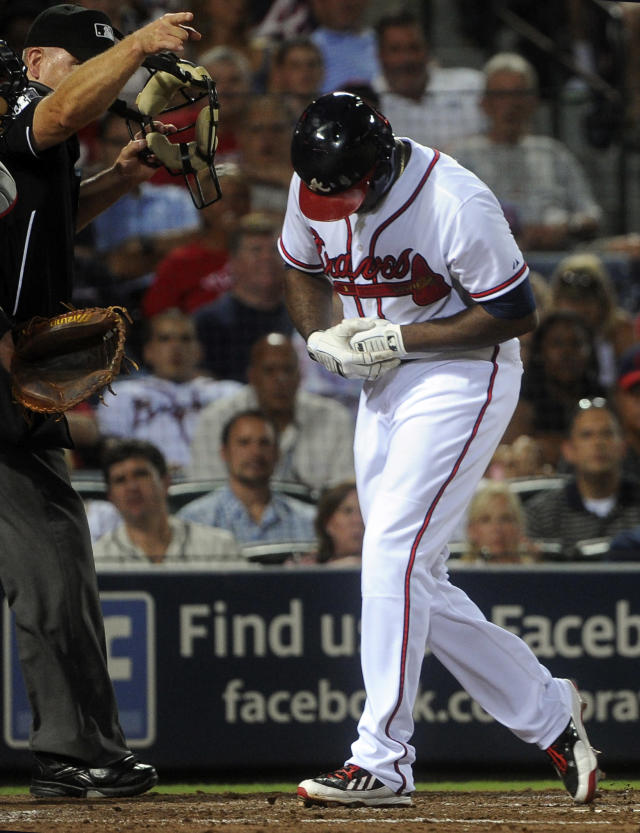 Atlanta Braves' Justin Upton, right, reacts after being hit by a pitch by starting pitcher Ubaldo Jimenez during the fifth inning of a baseball game on Thursday, Aug. 29, 2013, in Atlanta. Upton came out of the game on the play. (AP Photo/John Amis)