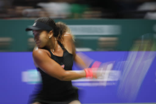 Naomi Osaka of Japan plays a return shot while competing against Kiki Bertens of the Netherlands during their women's singles match at the WTA tennis finals in Singapore, Friday, Oct. 26, 2018. (AP Photo/Vincent Thian)