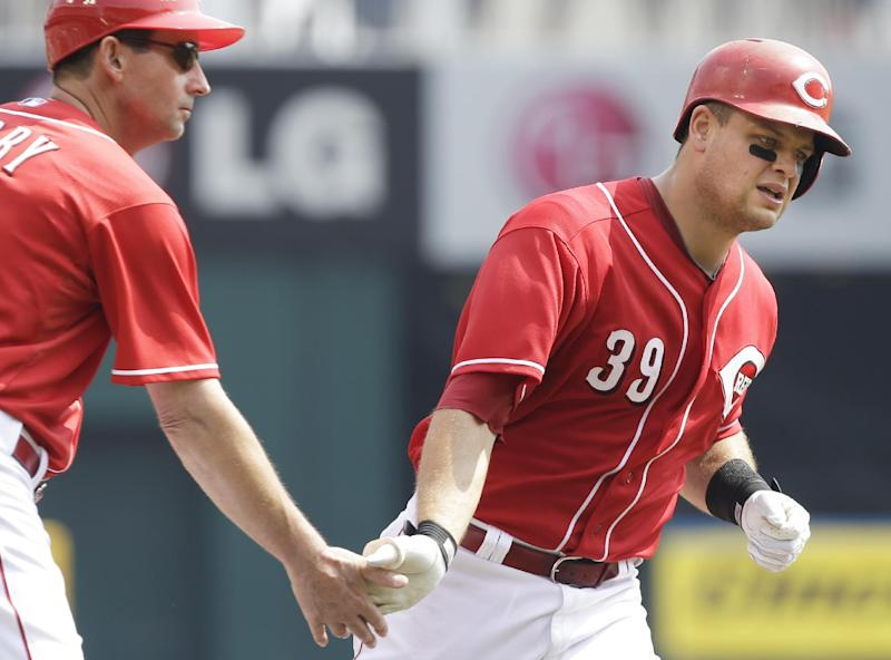 Cincinnati Reds' Devin Mesoraco (39) is congratulated by third base coach Mark Berry after hitting a solo home run off Chicago Cubs starting pitcher Jeff Samardzija in the fourth inning of a baseball game, Wednesday, Sept. 11, 2013, in Cincinnati. (AP Photo/Al Behrman)