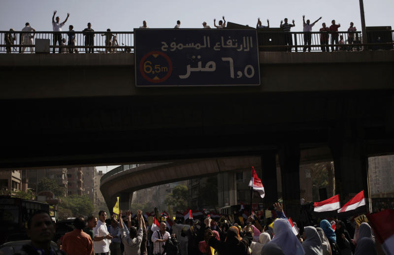 """Supporters of Egypt's ousted President Mohammed Morsi chant slogans against Egyptian Defense Minister Gen. Abdel-Fattah el-Sissi and hold placards showing an open palm with four raised fingers, which has become a symbol of the Rabaah al-Adawiya mosque, where Morsi supporters had held a sit-in for weeks that was violently dispersed in August during a protest in Cairo, Egypt, Friday, Oct. 4, 2013. The traffic sign on the bridge reads, """"The allowable height 6.5 Meters."""" (AP Photo/ Khalil Hamra)"""