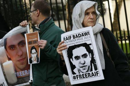 Demonstrators hold placards during a protest for Saudi blogger Raif Badawi, outside the Saudi Arabian Embassy in London