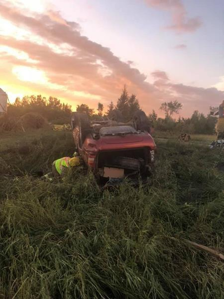 A first responder checks on an overturned vehicle at the scene where a tornado touched down, uprooting trees and overturning two vehicles near Virden, Man., in a Friday, Aug. 7, 2020, handout photo published to social media. THE CANADIAN PRESS/HO-Wallace District Fire Department, *MANDATORY CREDIT*