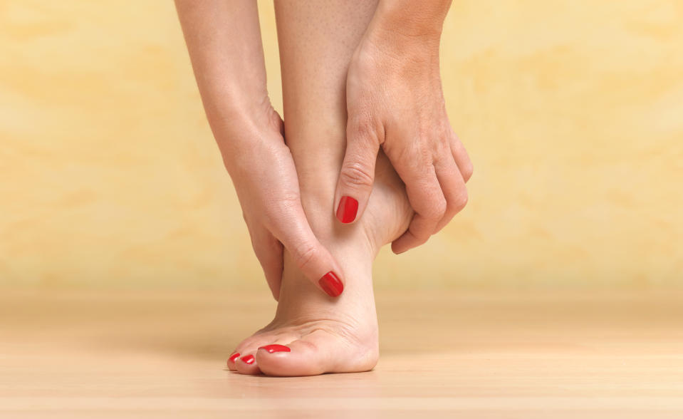 woman removed shoes to massage painful foot