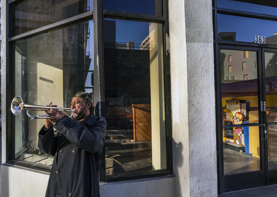 "FILE - In this Feb. 5, 2021, file photo, street musician Roberto Hernandez, originally from El Salvador, plays ""Lambada"" on his trumpet outside Buddy's, a restaurant temporarily closed due to the COVID-19 pandemic, in downtown Los Angeles. Los Angeles County could move into the next phase of reopening with fewer restrictions as early as next week, though any actual lifting of coronavirus-related constraints would not happen immediately, health officials said Wednesday, March 3, 2021. (AP Photo/Damian Dovarganes, File)"
