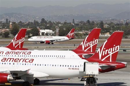 A Virgin America jet takes off past other aircraft parked at Terminal 3 at Los Angeles airport (LAX), California November 2, 2013