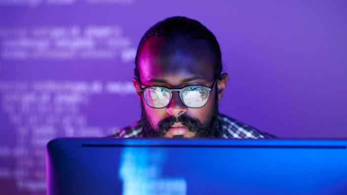 Young serious programmer in eyeglasses concentrating on working with coded data on computer screen.