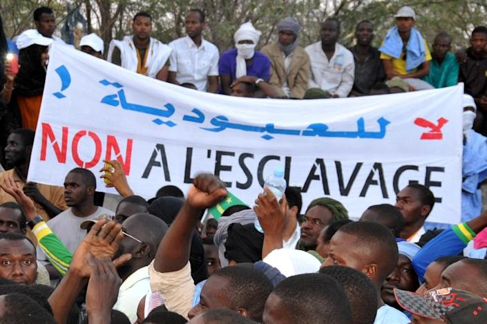 """People hold a banner reading """"No to slavery"""" during a demonstration in Nouakchott on April 29, 2015 (AFP Photo/)"""
