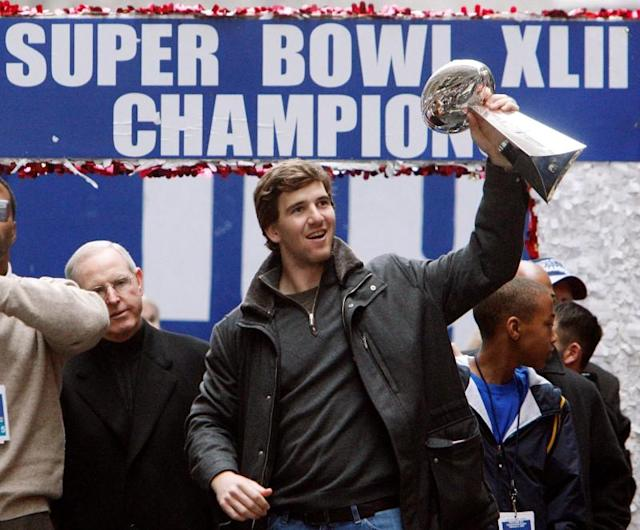 FILE PHOTO: New York Giants quarterback Manning holds the Vince Lombardi Trophy as he celebrates during a parade in honor of their win in the Super Bowl in New York