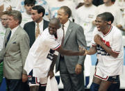 """FILE - In this Aug. 8, 1992, file photo, USA's Earvin """"Magic"""" Johnson, right, and Michael Jordan shake hands near the end of their 117-85 win over Croatia in the gold medal game in men's basketball at the Summer Olympics in Barcelona, as head coach Chuck Daly, left, and his assistant coaches Mike Krzyzewski, second left, and Lenny Wilkens, center, look on (AP Photo/John Gaps III, FIle)"""