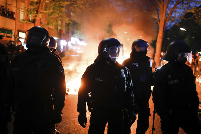 Police officers stand in front of a fire set up by demonstrators during a May Day rally in Berlin, Germany, Saturday, May 1, 2021. (AP Photo/Markus Schreiber)