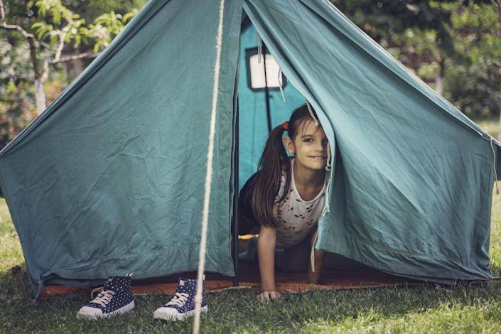 Cute girl playing in tent. Garden party. Summer fun. Child.
