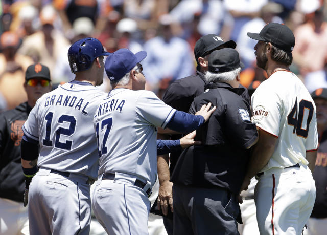 San Francisco Giants starting pitcher Madison Bumgarner, right, is restrained by a pair of umpires after throwing a close pitch to the San Diego Padres' Jesus Guzman during the second inning of their baseball game Wednesday, June 19, 2013 in San Francisco. At left is Padres catcher Yasmani Grandal and second from left is bench coach Rick Renteria. (AP Photo/Eric Risberg)
