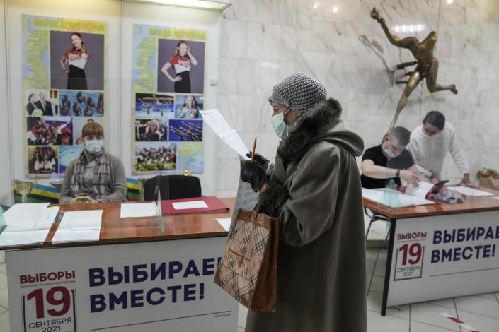 A woman prepares to cast her ballot at a polling station during a parliamentary elections in Moscow, Russia, Friday, Sept. 17, 2021. Russia has begun three days of voting for a new parliament that is unlikely to change the country's political complexion. There's no expectation that United Russia, the party devoted to President Vladimir Putin, will lose its dominance in the State Duma. (AP Photo/Pavel Golovkin)