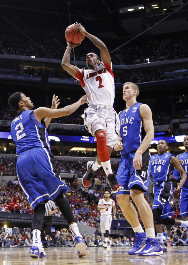 FILe - In this March 31, 2013 file photo, Louisville guard Russ Smith (2) goes up with a shot against Duke's Quinn Cook (2) and Mason Plumlee (5) during the first half of the Midwest Regional final in the NCAA college basketball tournament in Indianapolis. Smith was selected to The Associated Press' preseason All-America team, released Monday, Nov. 4, 2013. (AP Photo/Michael Conroy, File)
