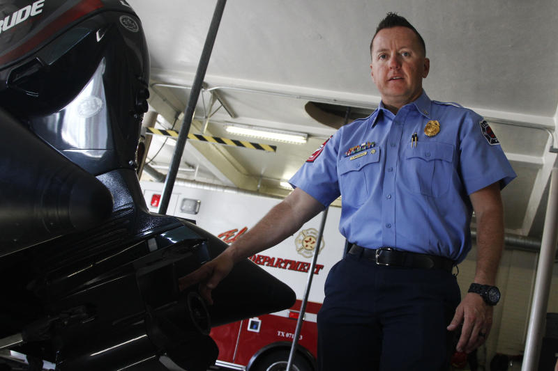 """CORRECTS LAST NAME ON FIRST REFERENCE TO MENENDEZ FROM MENDOZA - In this June 13, 2019, photo, firefighter Capt. Kris Menendez shows the plastic propeller on the engine of a rescue boat used in the Rio Grand and adjacent water canals in El Paso, Texas. """"They don't realize that once they get in there, they're feet can get swept away. There's a lot of obstacles, there's debris in the canal, and there are head gates,"""" Menendez said. The team was training near a head gate on June 11 when one of the firefighters spotted a body in the water. (AP Photo/Cedar Attanasio)"""