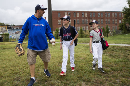 David Fox, from left, walks with his sons Dewey and Jimmy to a nearby baseball field from their house in northeast Washington, Friday, Aug. 23, 2019. David Fox and his wife, Mary Ann, have a rule for their sons, 11-year-old Dewey and 8-year-old Jimmy: They have to play a team sport. The kids get to choose which one. Dewey tried soccer and Jimmy had a go at flag football, but every spring and fall, their first choice is baseball. (AP Photo/Manuel Balce Ceneta)