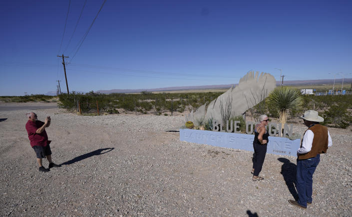 Albert Fehrenbach, left, makes a photo as his wife, Susan Fehrenbach, center, chats with Rick Pratt outside the entrance to the Blue Origin launch site near Van Horn, Texas, Monday, Oct. 11, 2021. Tuesday's launch has been pushed to Wednesday due to weather. (AP Photo/LM Otero)