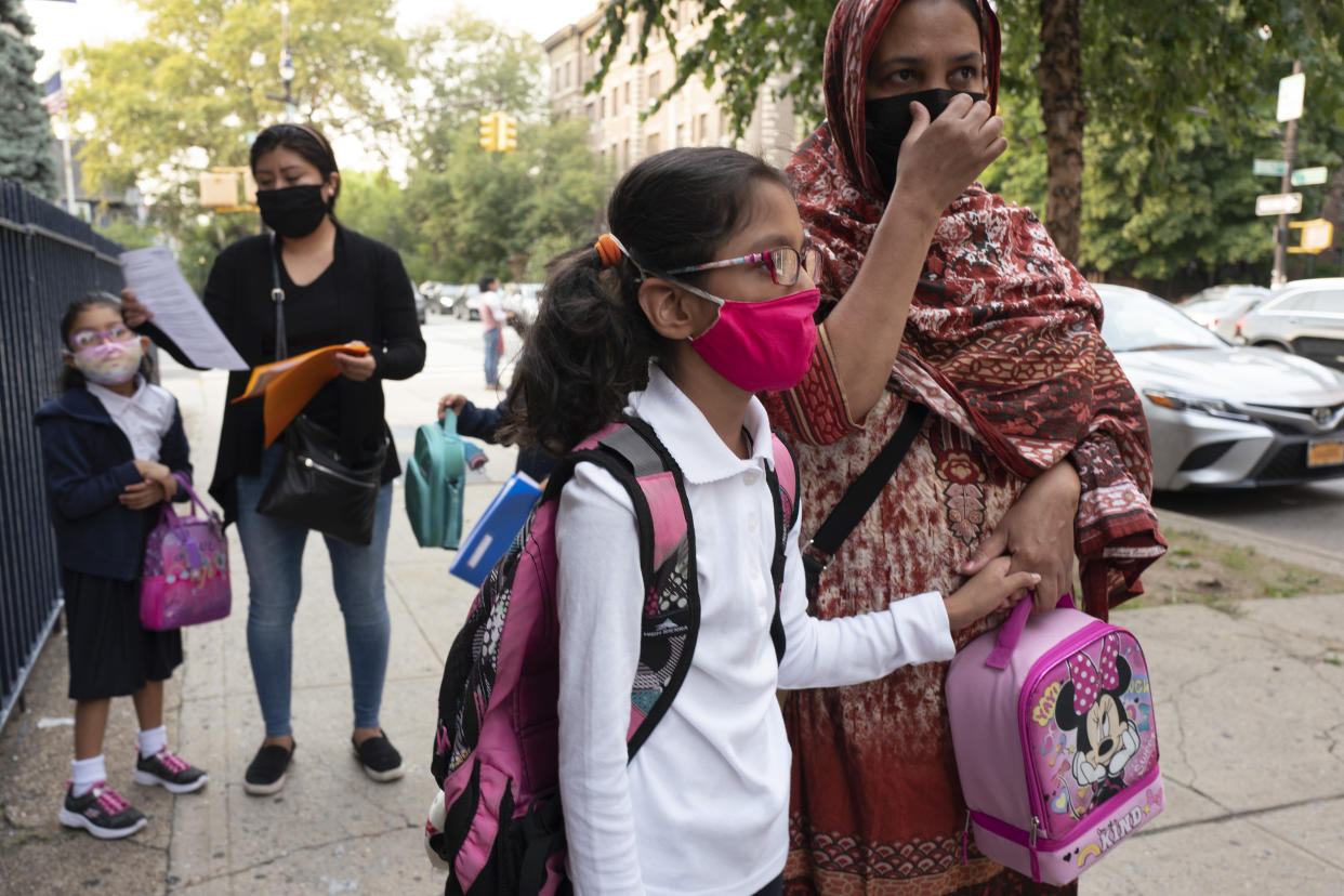 Children with backpacks and lunch containers stand with their parents on a sidewalk, all wearing face masks.