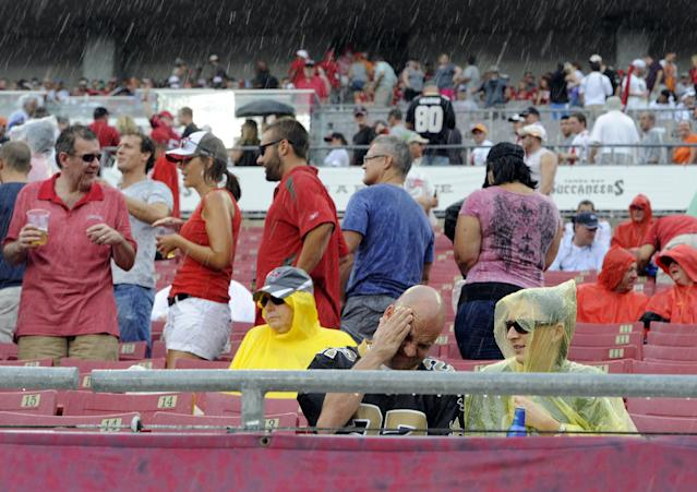 Football fans reacts to a weather delay as rain and lightning halt an NFL football game between the Tampa Bay Buccaneers and the New Orleans Saints, Sunday, Sept. 15, 2013, in Tampa, Fla. (AP Photo/Brian Blanco)