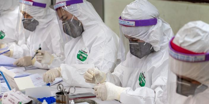 Medical specialists in protective suits work on blood samples collected for a coronavirus (COVID-19) rapid test from people who recently returned from Da Nang City on July 31, 2020 in Hanoi, Vietnam.