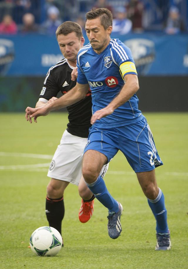 Philadelphia Union's Jack McInerney puts the pressure on Montreal Impact's Davy Arnaud during the first half a MLS soccer game in Montreal Saturday, Oct. 19, 2013. (AP Photo/The Canadian Press, Peter McCabe)