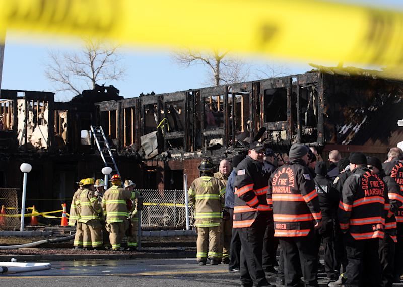 Firefighters investigate an early morning fire at the Mariner's Cove Hotel in Point Pleasant Beach, N.J. on Friday, March 21, 2014. An early morning fire killed three people at the Jersey shore motel whose residents included Superstorm Sandy victims who were staying there because their homes remain uninhabitable nearly a year and a half after the storm, officials said. Three other people were critically injured in the blaze. Authorities said several other people may be unaccounted for. Investigators are interviewing motel management to determine how many people were staying there when the fire broke out. The motel's office was destroyed and most records were lost. (AP Photo/David Gard)