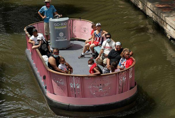 PHOTO: Visitors, some wearing masks to protect against the spread of COVID-19, ride a river barge along the River Walk, July 7, 2020, in San Antonio. (Eric Gay/AP)