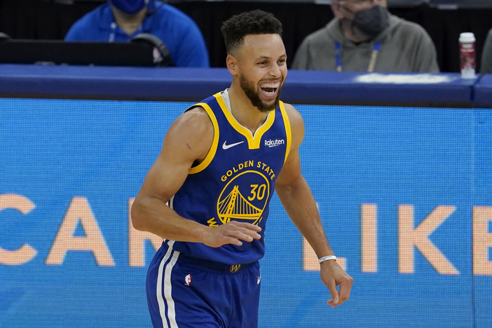 Stephen Curry smiles wide during a game.
