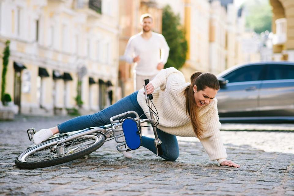 Woman on a city street falling with a bicycle on the road and a man running hurrying behind.