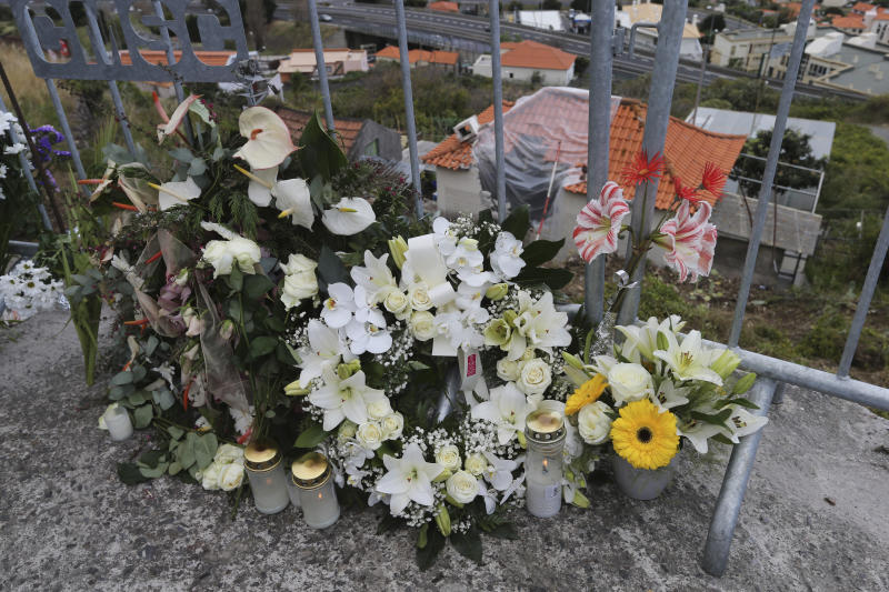 Flowers lie at the spot where a tourist bus veered off the road crashing into a house, seen below, killing 29 people in Funchal, the capital of Portugal's Madeira Island, Friday April 19, 2019. A German plane is expected to arrive Friday in Madeira to take home survivors from the bus accident that killed 29 tourists after it veered off the road and plunged down a slope. All the deceased were German. The bus carried 55 people, including a Portuguese driver and guide. Sixteen people remain hospitalized, but authorities said all of them are out of danger. (AP Photo/Armando Franca)