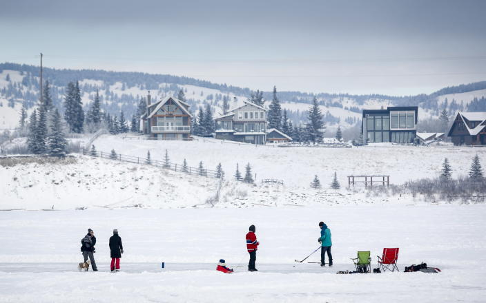 A family skates on a cleared area of ice on Ghost Lake Reservoir near Cochrane, Alberta, Canada, Sunday, Dec. 27, 2020, amid a worldwide COVID-19 pandemic. (Jeff McIntosh/The Canadian Press via AP)