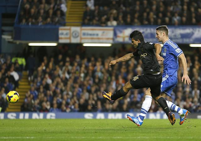 Manchester City's Sergio Aguero, left, scores a goal past Chelsea's Gary Cahill during the English Premier League soccer match between Chelsea and Manchester City at Stamford Bridge Stadium in London, Sunday, Oct. 27, 2013. (AP Photo/Kirsty Wigglesworth)